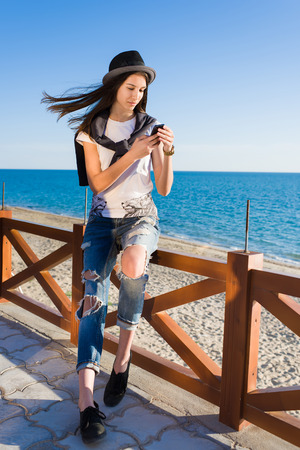 woman resting: Young female chatting on her mobile phone while enjoying sunny afternoon on the beach, woman reading text on the telephone while resting after promenade along the seashore, people using technology