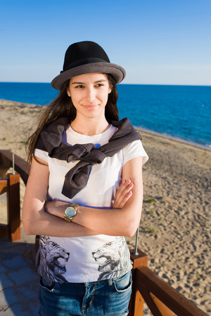 good weather: Portrait of a charming young woman enjoying a good weather and recreation time during the summer holidays, stylish female posing for the camera while looking aside on the beach in sunny day