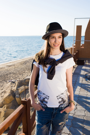good weather: Young beautiful female dressed in trendy clothes and stylish hat posing for the camera while standing on the beach in summer sunny day, gorgeous woman enjoying the good weather during spring vacations
