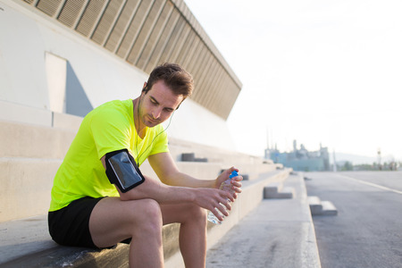 middle easter: Young sports build man sitting on concrete stairs while taking break after fitness training outdoors, middle easter male runner with bottle of water in the hands having rest after workout outside city Stock Photo