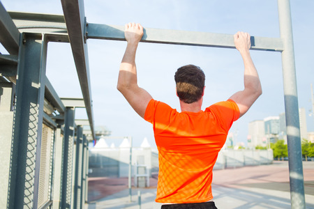 purposeful: Back view of purposeful sports man with strong body engaged in active sports while pull up on the horizontal bar outdoors, young male runner in bright t-shirt training hard in urban setting at sunset Stock Photo