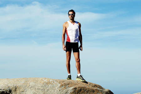 Full length portrait of mature sports man in workout wear standing on the hill of mountain rock while taking break after active fitness training, adult male runner resting after workout outdoors Stock Photo - 58106650