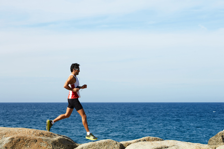 business for the middle: Full length portrait of handsome mature sports man running along the seashore while listening to music in headphones, male jogger while jumping over sea rocks while training hard outdoors in sunny day Stock Photo