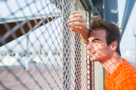 metal fence: Portrait of caucasian sports man leaning on urban metal fence while rest after active training and enjoying beautiful sunset, young thoughtful caucasian male runner taking break after workout outdoors