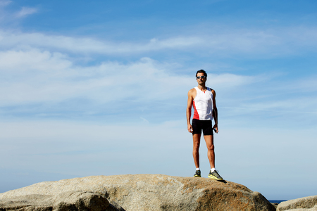 Full length portrait of exhausted male runner taking break after an active training in mountain landscape front while listening to music in headphones, mature sports man resting after active run