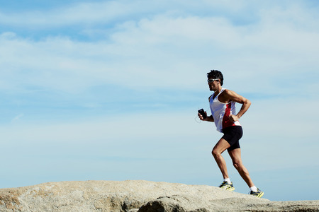 Full length portrait of young sports man running in mountain against beautiful sky with copy space area for your text message or advertising content, male runner listening to music in headphones