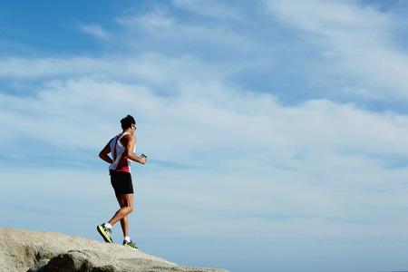 escucha activa: Retrato de cuerpo entero de correr corredor masculino en la roca de la monta�a mientras se escucha m�sica en los auriculares, atleta masculino haciendo un entrenamiento activo en fondo del cielo con �rea de espacio de copia para el mensaje de texto