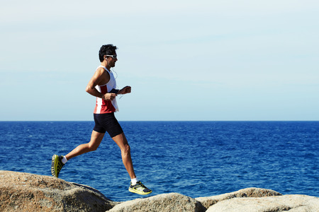 people listening: Side view of mature man runner with perfect body jogging along the sea and jumping over big rocks while listening to music in headphones, handsome sportsman in sportswear doing an active workout outdoors