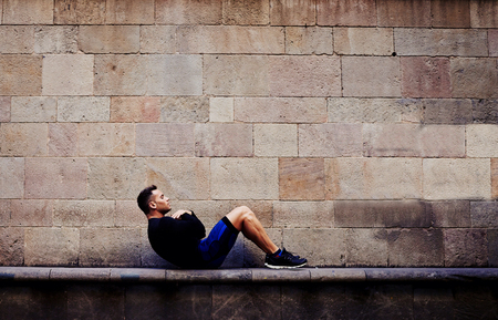 abdominal wall: Side view of young sportsman doing abdominal crunches against brick wall with copy space area for your text message or advertising content, sporty guy engaged an intensive fitness training in urban setting Stock Photo