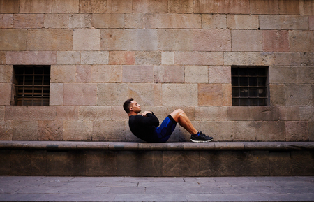 abdominal wall: Young muscular build man doing crunches outdoors in antique city, male athlete in sportswear doing exercising for abdominal against brick wall with copy space area for your text message or content