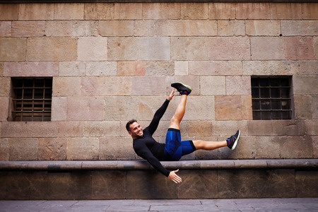 abdominal wall: Side view of handsome male athlete doing exercising for legs while lying on a concrete bench, smiling sportsman doing workout outdoors against brick wall with copy space area for text message or content