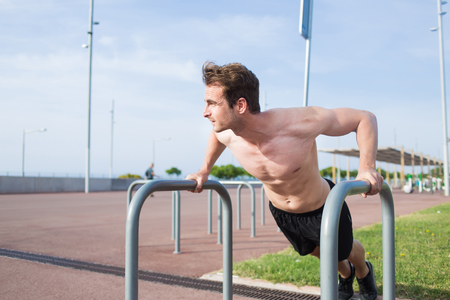 outworn: Young muscular build man shirtless doing push-ups exercise outworn on iron pipes gym equipment, handsome male runner warming up before began his morning workout training Stock Photo