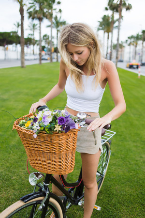 sweden resting: Portrait of a attractive young blonde woman preparing for ride in the park on her classic bicycle, pretty female in stylish clothes enjoying weekend strolling on vintage bike with basket of flowers