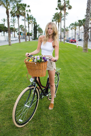 sweden resting: Full length portrait of a trendy woman standing in the park on green grass with her vintage bike enjoy weekend recreation,wonderful caucasian model posing with retro bicycle with basket of flowers and