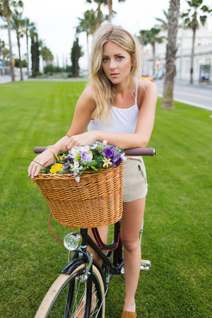sweden resting: Lovely hipster girl looks at camera while standing in the park on a green lawn with her classic bicycle with basket of beautiful flowers, attractive young woman enjoying leisure during summer vacation