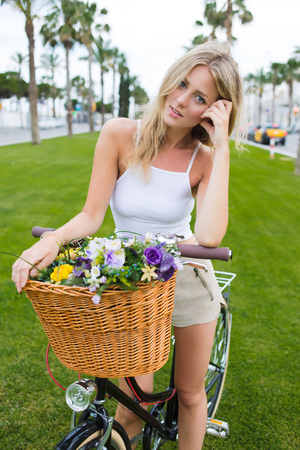prettiness: Portrait of pretty face young woman standing in the park with her classic bicycle and looks at the camera, gorgeous woman enjoying holidays strolling on bike with basket of beautiful summer flowers