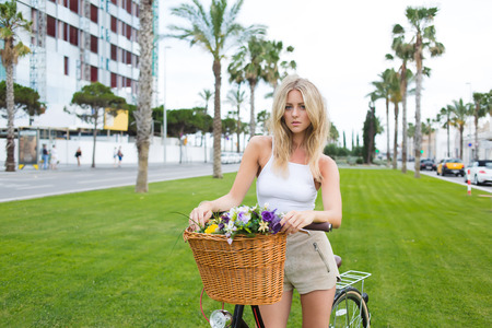 prettiness: Half length portrait of lovely stylish hipster girl posing in the park with her vintage bicycle with a basket of summer flowers, Sweden female rest after riding through the city during summer holidays