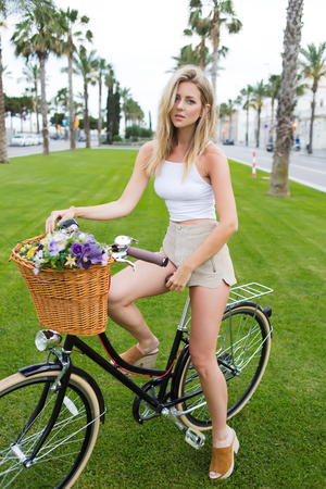 prettiness: Full length portrait of a gorgeous female dressed in trendy clothes standing outdoors with her retro bicycle and looks at you, attractive blonde hair woman posing for the camera with vintage bike