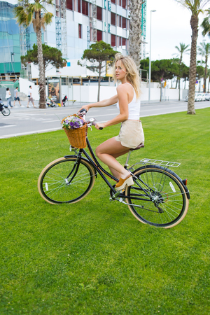 enjoy space: Charming young woman cyclist enjoy the ridingin the park on her vintage bike with a basket of flowers, female ride on bicycle over a green lawn background with copy space area for your text message Stock Photo