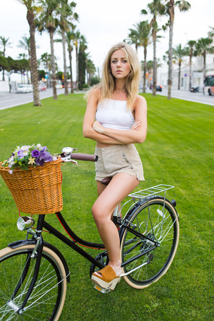 sweden resting: Trendy caucasian woman in stylish clothing sitting on her vintage bike in pose with hands crossed while standing on the green grass in the park, wonderful female posing with classic bicycle outdoors