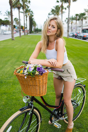 area sexy: Portrait of a young beautiful woman leaning on her retro bicycle with a basket of flowers in the street on a green lawn, gorgeous fashion female posing for the camera in a summer day during weekends