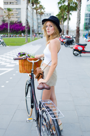 area sexy: Young hipster girl dressed in glamorous stylish clothes standing on the street with classic bicycle while rest after riding in the city,charming fashion female posing for the camera with vintage bike