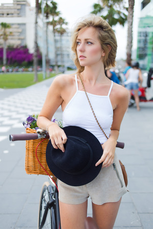 sweden resting: Caucasian blonde hair fashionable female dressed in stylish clothes standing with her vintage bike outdoors, charming woman cyclist resting after riding around the city during the summer holidays