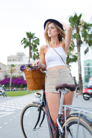 sweden resting: Portrait of a glamorous tourist woman enjoying summer vacation riding on retro bicycle with a basket of flowers, trendy female cyclist standing in the street with her vintage bike and looking aside