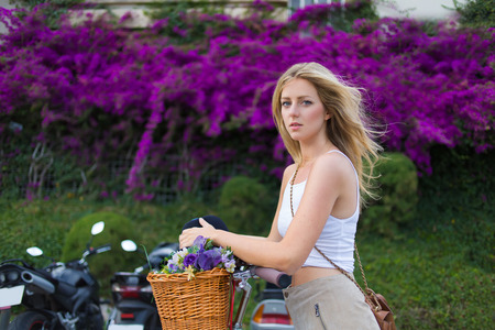 prettiness: Portrait of charming stylish caucasian female enjoy a rest after an active riding through the city on her classic bicycle, woman standing against beautiful flowers and greenery fence with copy space