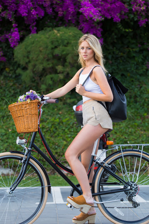 area sexy: Full length portrait of fashionable young hipster girl riding in urban setting on her retro bike with a basket of beautiful flowers, glamorous woman enjoying recreation time while strolling on bicycle Stock Photo