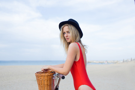 area sexy: Young pretty caucasian female dressed in fashionable swimwear posing for the camera while standing on the beach with retro bicycle against sea and sky background with copy space area for your content Stock Photo