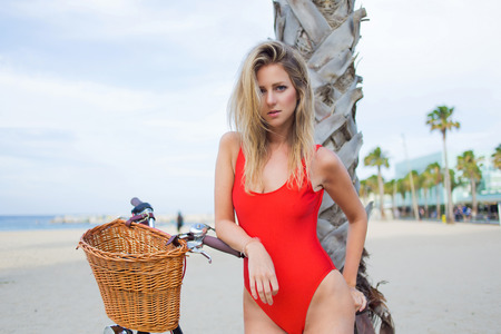 half dressed: Half length portrait of young sexy woman dressed in trendy swimsuit standing on the beach with her vintage bike, attractive female in swimwear enjoying rest in summer holidays strolling with bicycle