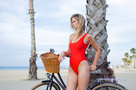 area sexy: Young charming woman in bikini resting after ride on her retro bicycle along the beach, attractive female standing with vintage bike on coastline enjoying beautiful landscape of the sea in summer day Stock Photo