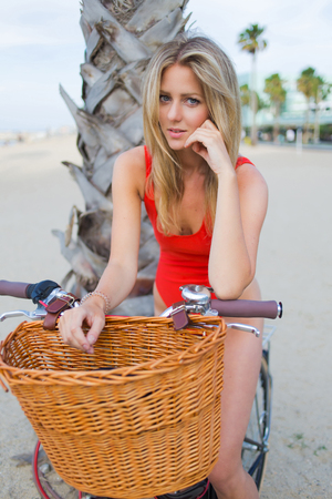 prettiness: Portrait of a gorgeous woman dressed in fashionable swimwear sitting on her vintage bike enjoying rest after riding,attractive female in bikini posing for the camera on the beach in California Stock Photo