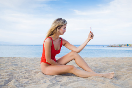 prettiness: Young sexy woman dressed in fashion bikini using mobile phone camera for take a picture of herself while sitting on the beach ,charming young female in swimwear taking self portrait with smart phone