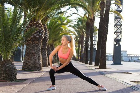 female jogger: Portrait of a young female jogger stretches legs muscles before a fitness training on the fresh air outside, charming sports woman with beautiful slim figure working out outdoors in sunny summer day