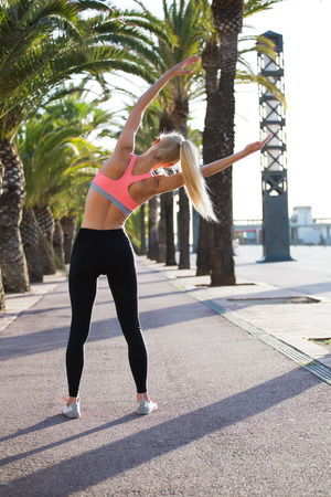 female jogger: Full length portrait of a fit woman with perfect figure doing warm up exercising outdoors in summer day, female jogger dressed in sports wear doing stretches exercise before began her morning running