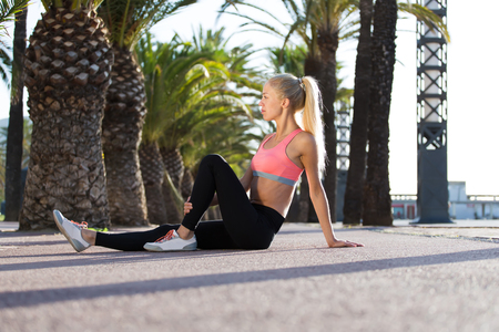 rest day: Young beautiful fit woman with perfect slender body enjoying rest after workout outdoors, athletic female in sportswear took a minute break after fitness training outside in sunny summer day outside