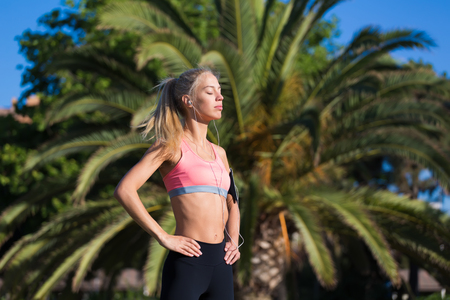 female jogger: Half length portrait of young female jogger closed her eyes enjoying the sun and rest after morning run, fit caucasian woman listening to music in headphones while taking break after workout outdoors