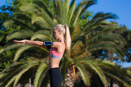 half dressed: Half length portrait of female runner with armband on the hand listening to music in headphones while doing physical exercise in sunny summer day outdoors, fit woman dressed in sport wear working out Stock Photo