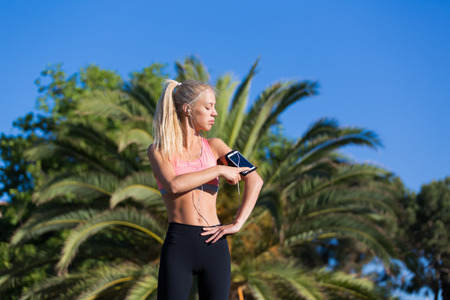 day break: Half length portrait of athletic female touching screen of smart phone in running armband while listening music in headphones, fit woman taking break after workout outdoors in sunny summer day Stock Photo