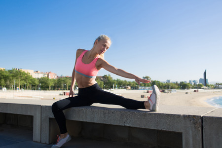 athletic wear: Fit woman in sport wear stretches leg while sitting on pier against blue sky background with copy space area for your text message or advertising content, athletic female at physical exercise outdoors