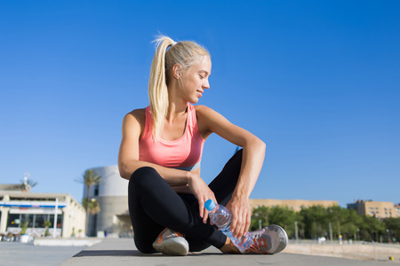 female jogger: Portrait of an attractive female jogger with cute smile enjoy rest after workout against blue sky with copy space for your text message or content, young fit woman in sportswear taking break after run
