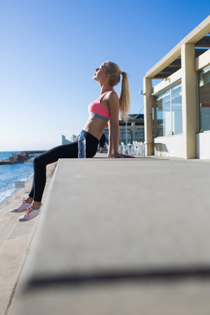 female jogger: Young fit woman with eyes closed enjoying the sun while taking break after physical exercise in summer day,female jogger dressed in sport wear resting after fitness training with copy space for text