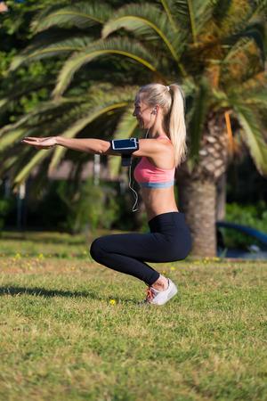en cuclillas: Retrato de cuerpo entero de la hembra joven atlético con el funcionamiento de brazalete en cuclillas haciendo ejercicio en la palma de la mano parque de árboles, encaja mujer caucásica escucha música en los auriculares mientras se trabaja al aire libre