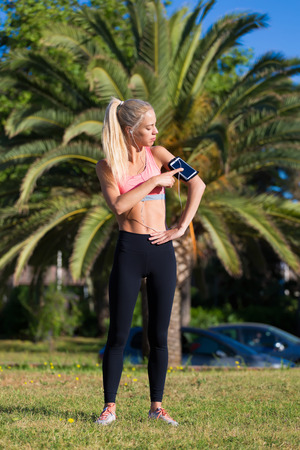 female jogger: Full length portrait of young athletic female touching phone screen in arm sport band while taking break after morning run, female jogger dressed in tracksuit resting after fitness training outdoors
