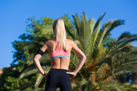 activewear: Rear view shot with female jogger with perfect figure taking break after morning run standing back to camera in palm park, young woman dressed in sports wear resting after fitness training outdoors Stock Photo