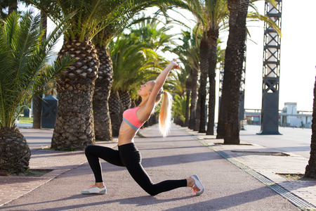 out of body: Portrait of a young sports woman with slender figure working out outdoors in sunny summer morning, athletic female with perfect body in sportswear do warm up exercise before morning run outdoors