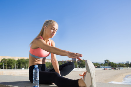 female jogger: Young fit woman stretching leg while sitting on the concrete pier against blue sky background with copy space area for your text message or advertising content, female jogger working out outdoors