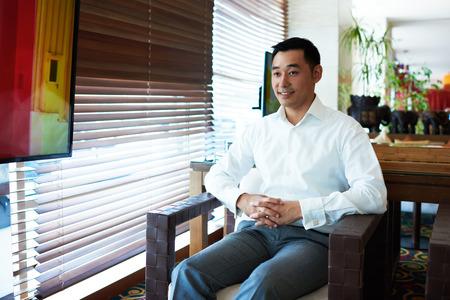 若いアジアのオフィス ワーカーの肖像服を着て企業成功したビジネスマンの笑みを浮かべてモダンなレストランのインテリアに座って楽しむ無料時